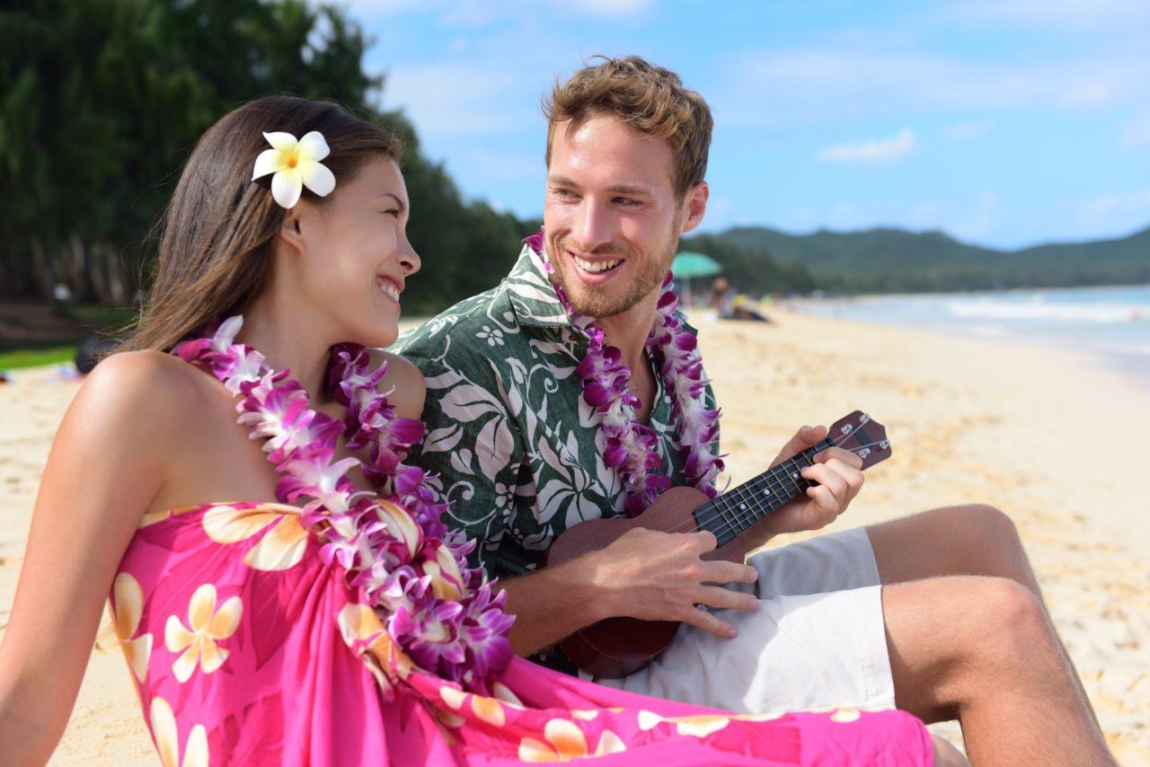 couple honeymooning on a beach in hawaii, man playing ukulele
