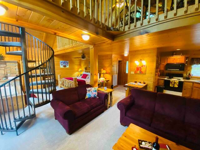 Cabin living room with plush furnature and spiral staircase