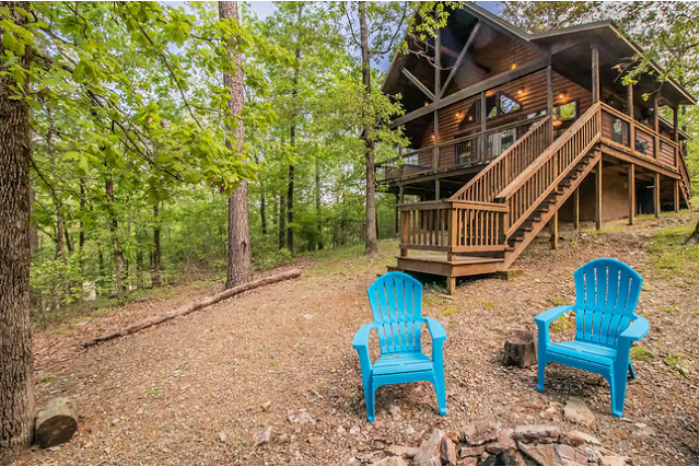 firepit with 2 chairs and cabin in background